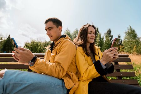 smiling young couple in yellow jackets sitting on bench in autumn Park using phones, smartphones. Millennials, inseparable from gadget, device