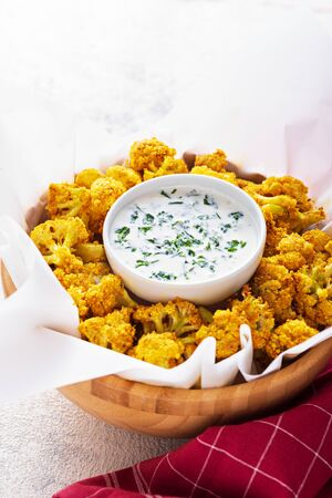 oven baked cauliflower with sauce and herbs on wooden plate on light background. vegetable side dish concept