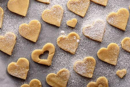 top view uncooked heart shaped cookies on parchment white paper sprinkled with powdered sugar Stock Photo