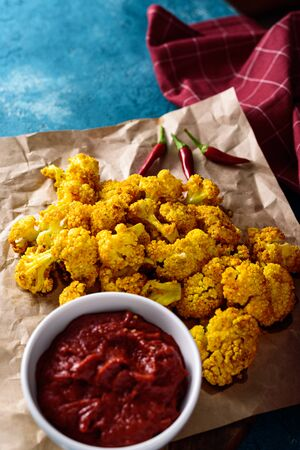 vertical baked cauliflower on Kraft paper with tomato sauce and chili peppers blue background