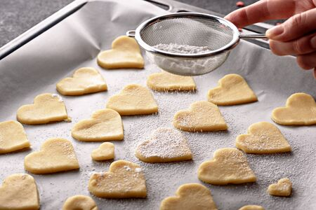 close up cookies hearts on parchment paper on baking sheet sprinkle powdered sugar on top through strainer