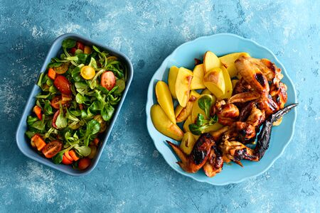 top view fried chicken wings in soy sauce marinade with potatoes and vegetable salad on blue background