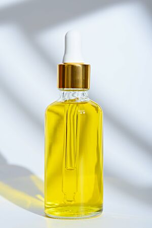 vertical dropper glass bottle with yellow cosmetic oil on white background