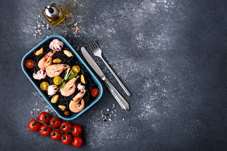 top view black pasta with seafood-shrimp, mussels, octopus, cherry tomatoes in blue plate on gray background with copy space Banque d'images
