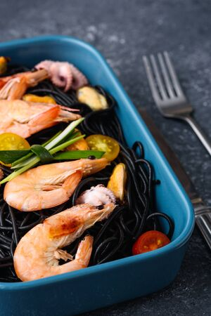 closeup black pasta with seafood-king prawns, mussels, octopuses, cherry tomatoes in blue plate with fork on gray background