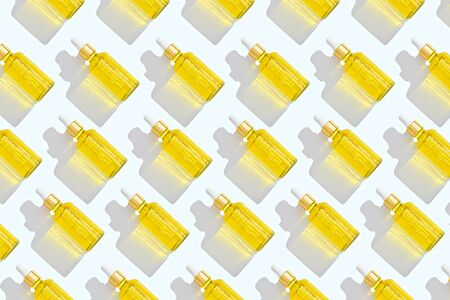 trendy pattern of dropper bottles with white pipette and yellow liquid on white background Stock Photo