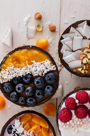 vertical top view four colorful smoothie bowls with blueberries, raspberries, physalis and coconut shavings in coconut bowls on white background, trendy desserts concept