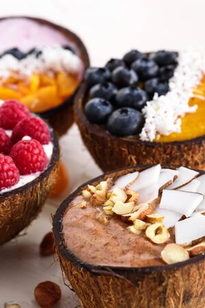 closeup four trendy smoothie bowls with berries, fruit, nuts in coconut bowl on wooden table, vegetarian dessert