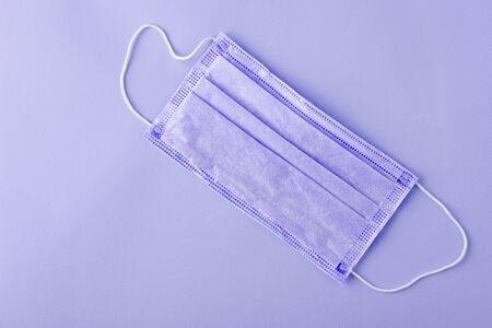 one tinted medical mask on lilac background, top view, flat lay, copy space, medical protection products concept