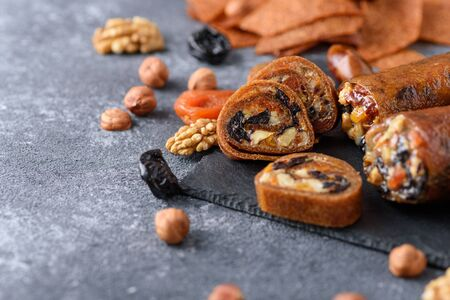 closeup fruit roll-up with nuts, prunes, dried apricots and honey, vegetarian snack, healthy bar on gray background, oriental sweets, copy space