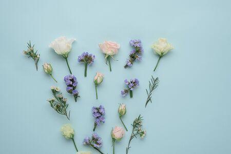 rose buds, eustoma, limonium inflorescences on blue background, flower arrangement, bouquet of flowers, top view, flat lay, floral composition Reklamní fotografie
