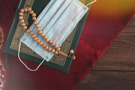blue medical mask on Koran with wooden prayer beads on red carpet, Ramadan under quarantine concept, top view, copy space Banque d'images