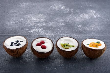 ice cream in coconut bowls with berries in row on gray background, smoothie bowl concept, trendy dessert, copy space