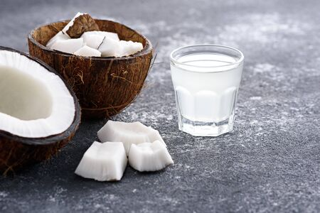 trendy coconut water in glass, coconut halves on gray background, closeup Banque d'images