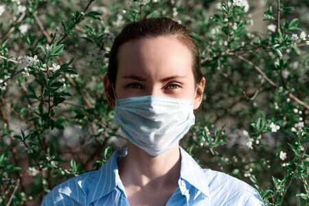 brunette woman in medical mask in Park, allergic concept, coronavirus, Allergy to blooming Banque d'images