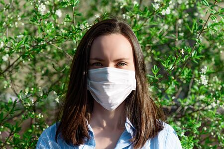 caucasian brunette woman in medical mask in Park, coronavirus, Allergy to blooming, health care