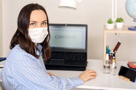 woman in medical mask wrote word covid-19 on monitor screen, remote work at home, coronavirus, pandemic, news