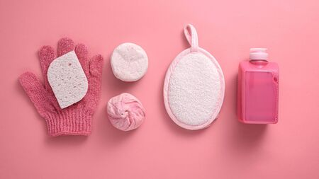washcloth, sponge, gel, soap, salt on pink background, bath and Spa day concept, top view, flat lay, wellness concept Foto de archivo