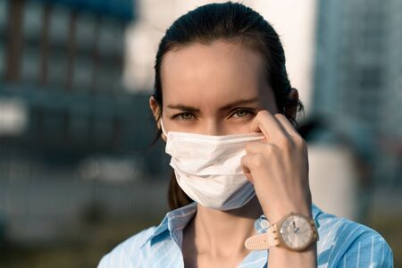 caucasian woman adjusts medical mask on face with hand, allergies, coronavirus
