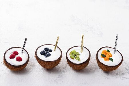 milkshakes with berries and tubes in coconut bowls on white background, ice cream, trendy food, copy space