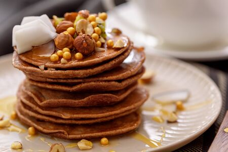 closeup chocolate pancakes in beige plate with nuts, kiwi and coconut flakes, trendy breakfast concept