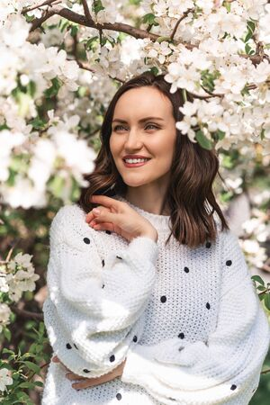 portrait of smiling woman in white jumper near blooming Apple tree, closeup