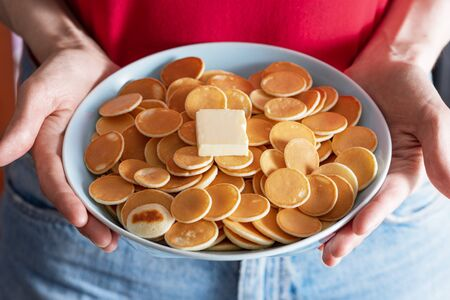 closeup cereal pancakes in blue bowl with piece butter in women's hands Banque d'images