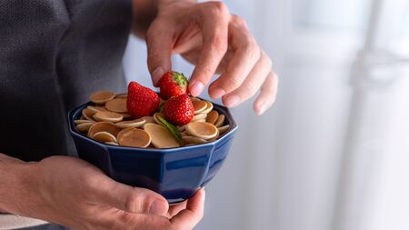 closeup cereal pancakes in blue bowl with piece butter in men's hands, trendy food concept Stock Photo