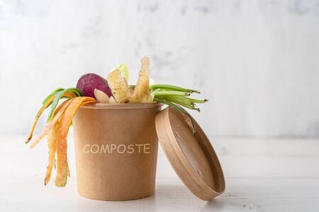 vegetable peels in an eco-friendly cardboard box on white wooden background, compost concept, biodegradable organic products, food waste recycling Banque d'images - 149177091
