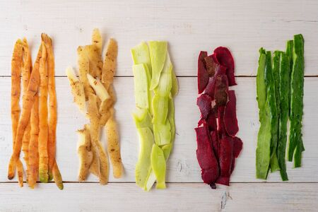 vegetable peels on white wooden background, compost concept, recycling of food waste, top view, flat lay Banque d'images