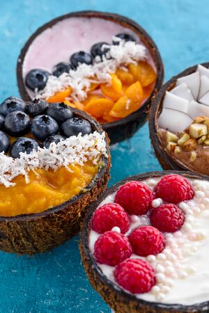 exotic ice cream with berries in coconut bowls on blue background, trendy smoothie bowl, dessert