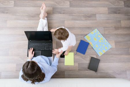 top view brunette woman with laptop and child sitting on floor, remote work at home, freelancer concept