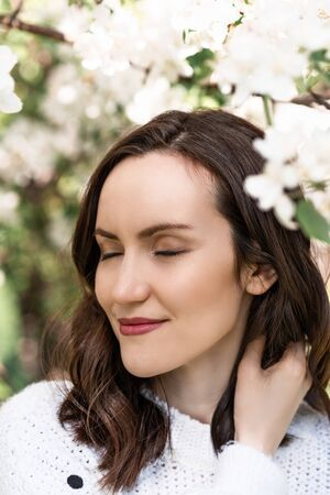 portrait of beautiful girl, woman brunette with closed eyes near blooming Apple tree, spring time Banque d'images