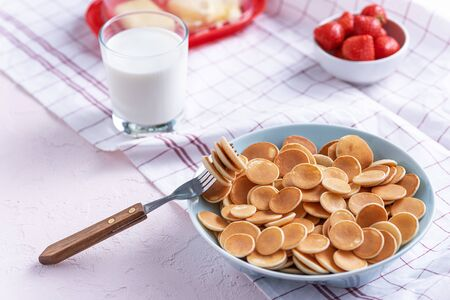 mini cereal pancakes in blue bowl with fork, strawberries, glass of milk on white background, rural Breakfast concept, trendy food