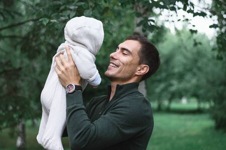 dark-haired dad in green jacket with infant baby in hands, happy fatherhood, unconditional love concept