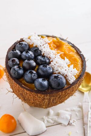 smoothie bowl with mango, blueberry and coconut shavings in coconut bowls on white background, mango sherbet, closeup