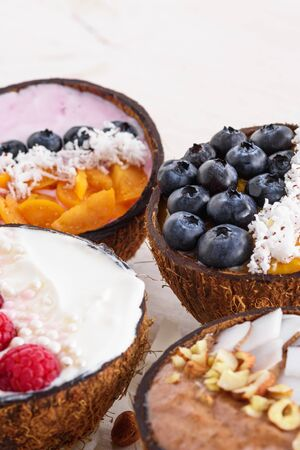 exotic smoothie bowls with berries in coconut bowls on white background, trendy dessert, closeup