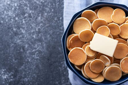 trendy cereal pancakes in blue bowl with buttering toast on blue gauze on grey background, copy space, top view Banque d'images