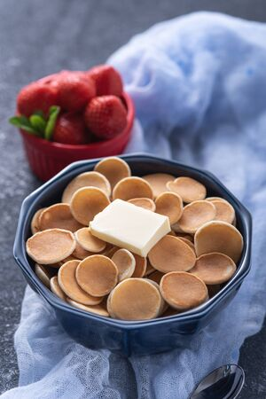 trendy cereal pancakes in blue bowl with buttering toast and strawberry on blue gauze on grey background, closeup