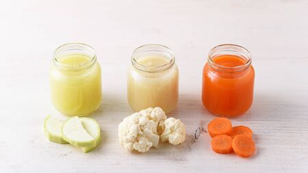 natural vegetable baby food in glass jars with zucchini, cauliflower, carrots on white background, homemade organic food Banque d'images