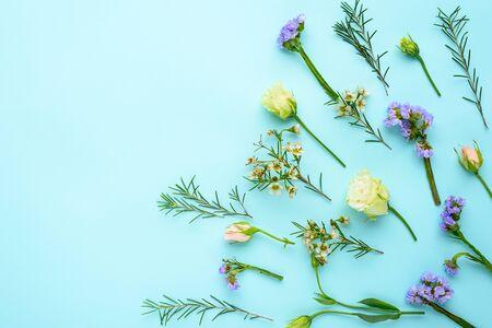 summer flower arrangement on blue background, top view, flat lay