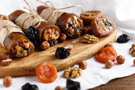 closeup rolls with dried fruits, oriental sweets on white background, roll-up with dried apricots, prunes, walnut Banque d'images