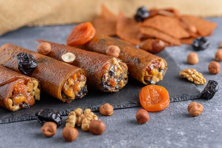 rolls with dried fruits, Eastern sweets on gray background, roll-up with dried apricots, prunes, nuts