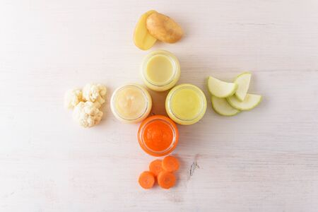 baby vegetable puree of carrots, zucchini, cauliflower, potatoes in glass jars on white background, homemade baby food concept, top view Stock Photo