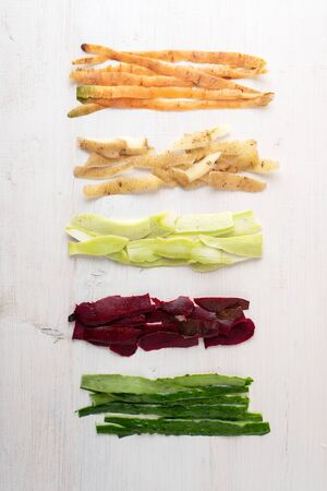 top view peel of carrots, potatoes, zucchini, beets, cucumbers on white background, compost concept, food waste
