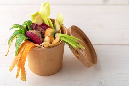 composting concept, vegetable peels in cardboard biodegradable container on white background, food waste