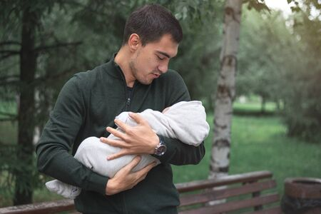 man brunette with newborn baby in arms in Park, happy long-awaited fatherhood concept