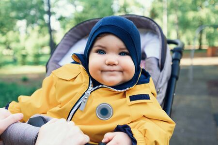 portrait of small toddler, baby in yellow jumpsuit sitting in stroller in Park, happy childhood concept Banque d'images - 149472922