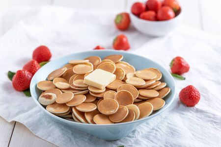 tiny cereal pancakes in blue plate with strawberries on white background, trendy food concept