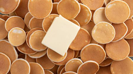 tiny cereal pancakes with piece of butter, pancakes background, top view Stock Photo